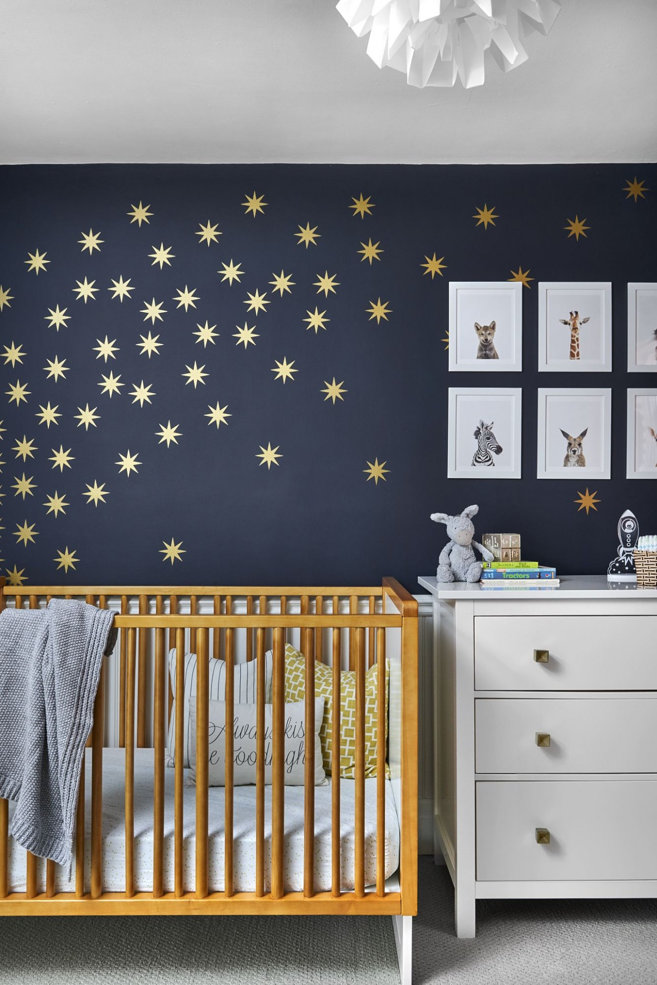 Beautiful nursery decor with navy blue wall and stars decal