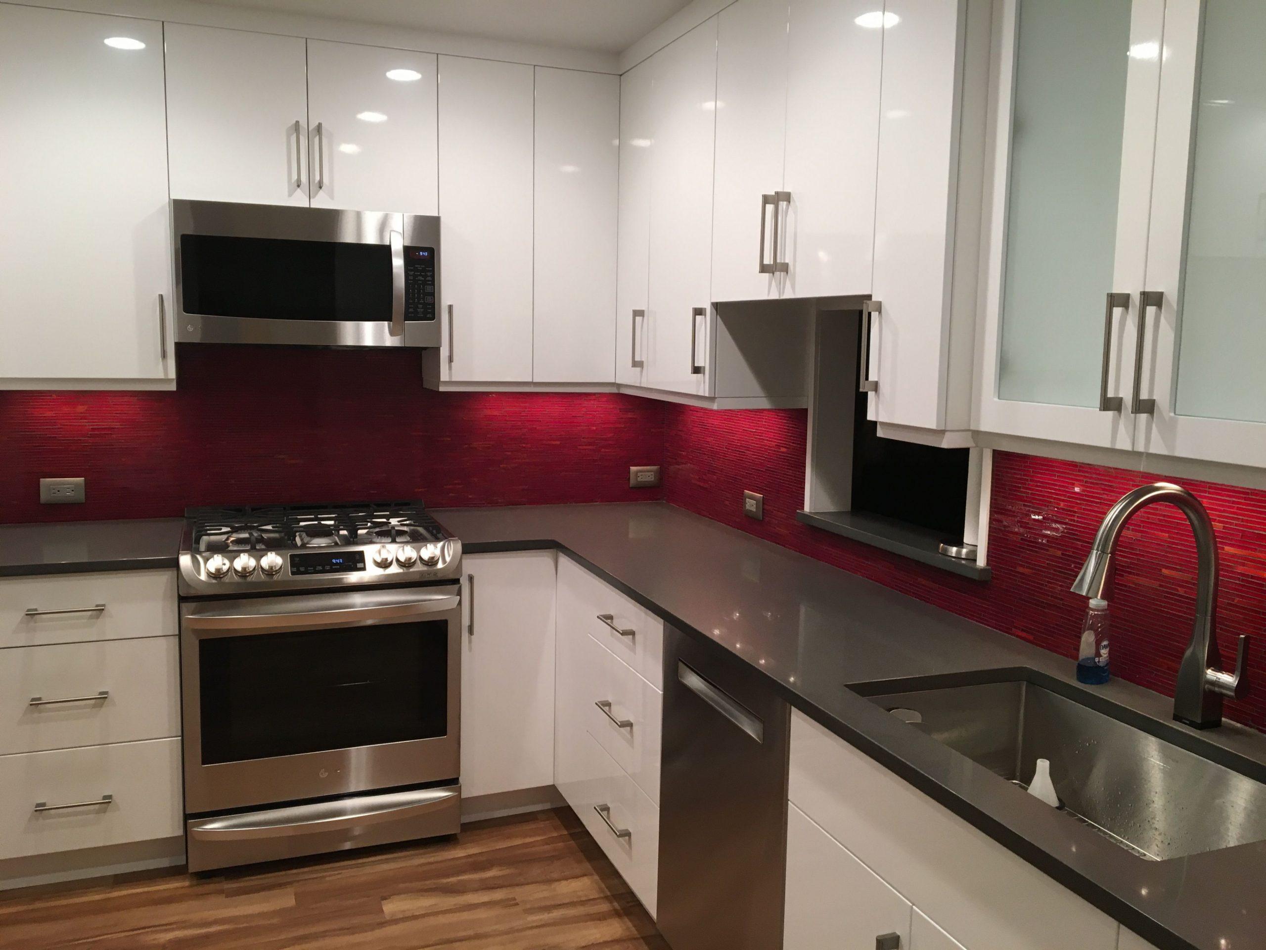 Modern, white kitchen cabinets with red glass backsplash