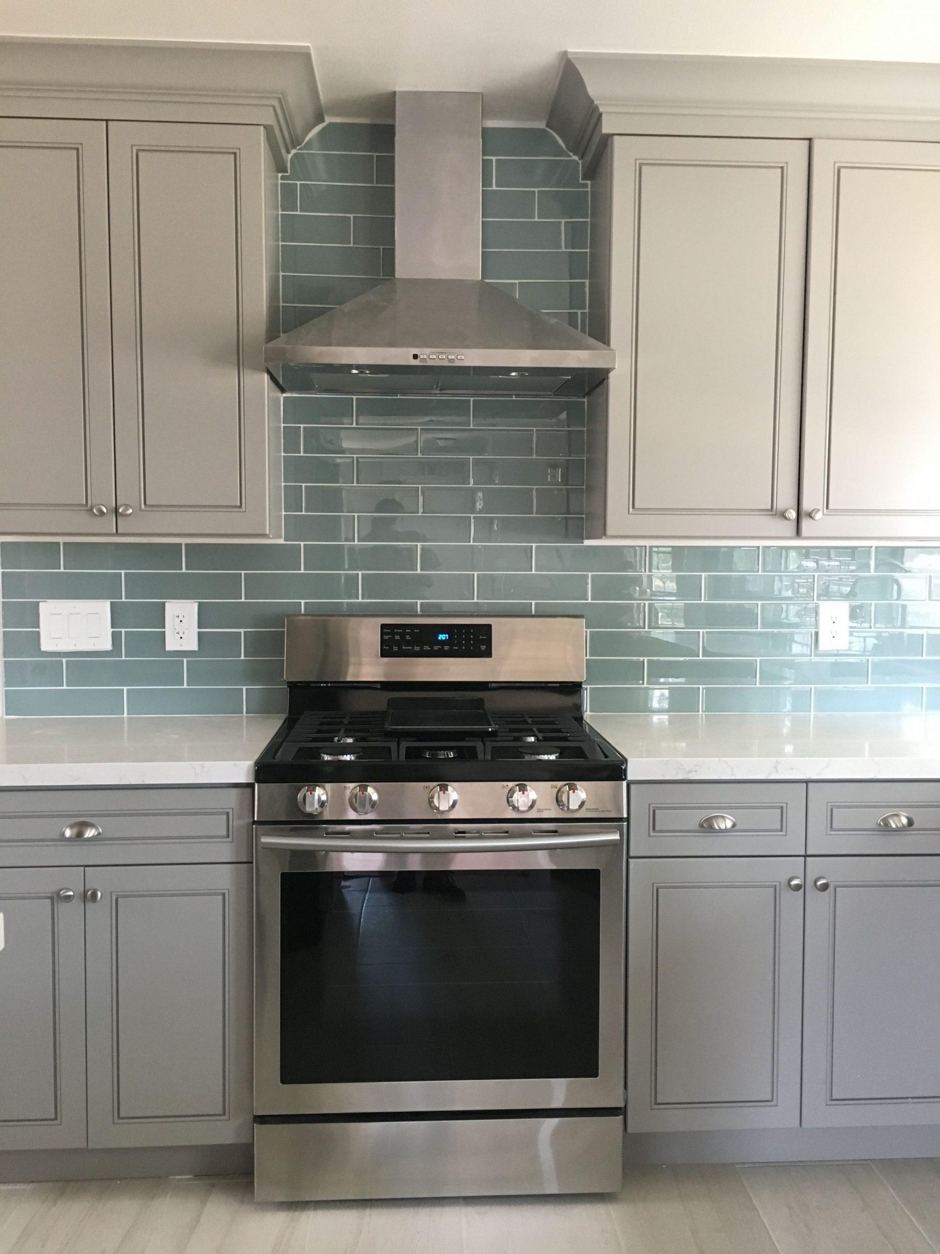Blue glass tile backsplash with gray cabinets and white quartz  - Gray Kitchen Cabinets With Blue Backsplash