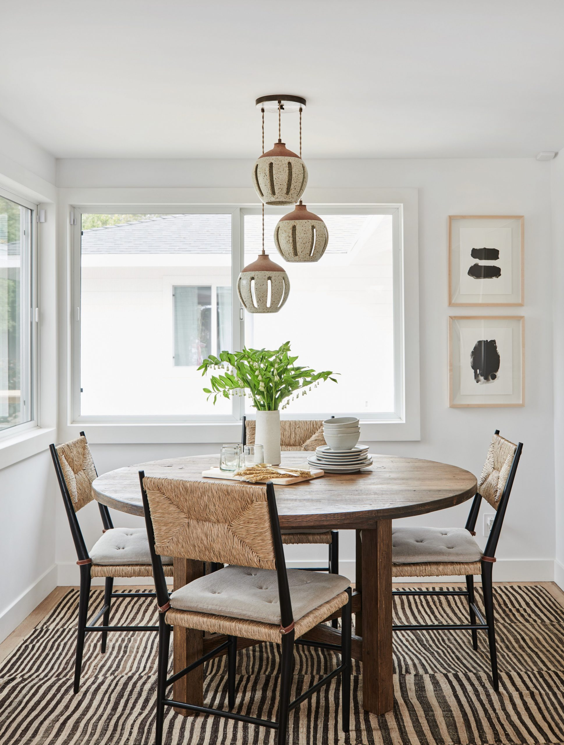 organic neutral dining room nook with vintage rug and woven chairs  - Neutral Dining Room Ideas